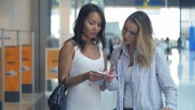 Lyckliga unga kvinnor med smartphone- och shoppingpåsar som talar i galleria Royaltyfria Bilder