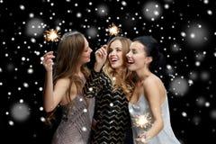 Lyckliga unga kvinnor med tomtebloss över snö Royaltyfria Foton