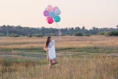 Lyckliga unga kvinnor med utomhus- ballonger royaltyfria bilder
