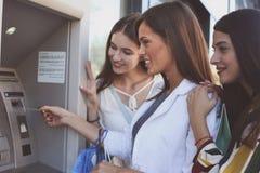 Lyckliga unga kvinnor som använder bankomaten Kvinnor som använder kreditkorten Arkivbilder
