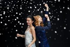 Lyckliga unga kvinnor som dansar över snö Royaltyfri Foto