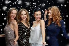 Lyckliga unga kvinnor som dansar över snö Royaltyfria Bilder