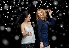 Lyckliga unga kvinnor som dansar över snö Arkivbild