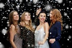 Lyckliga unga kvinnor som dansar över snö Fotografering för Bildbyråer