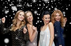 Lyckliga unga kvinnor som dansar över snö Arkivbilder