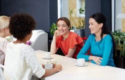 Lyckliga unga kvinnor som dricker te eller kaffe på kafét Royaltyfri Fotografi