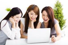 lyckliga unga kvinnor som håller ögonen på bärbara datorn i vardagsrum Royaltyfri Foto