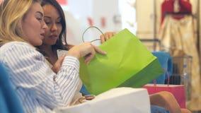 Lyckliga unga kvinnor som ser in i shoppingpåsar Arkivfoton