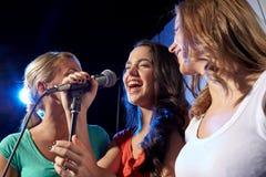 Lyckliga unga kvinnor som sjunger karaoke i nattklubb Arkivbild