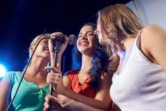 Lyckliga unga kvinnor som sjunger karaoke i nattklubb Fotografering för Bildbyråer