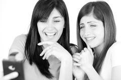 Lyckliga unga kvinnor som skrattar se bilder efter selfie med smartphonen royaltyfri fotografi