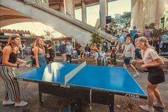 Lyckliga unga kvinnor som spelar bordtennis i folkmassa av vänner på klubban i stadsområde Royaltyfria Bilder