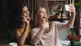 Lyckliga unga kvinnor som tar selfie i kafét som visar tummar-upp och reko gest stock video
