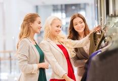 Lyckliga unga kvinnor som väljer kläder i galleria Arkivfoto