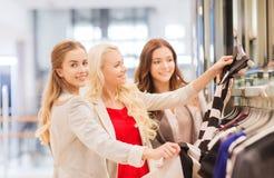 Lyckliga unga kvinnor som väljer kläder i galleria Arkivbild