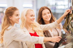 Lyckliga unga kvinnor som väljer kläder i galleria Royaltyfria Bilder