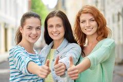 Lyckliga unga kvinnor som visar tummar upp på stadsgatan Arkivfoton