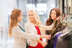 Lyckliga unga kvinnor som väljer kläder i galleria Royaltyfria Foton
