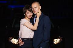 Lyckliga unga modepar som är förälskade bredvid bilen på natten arkivfoton