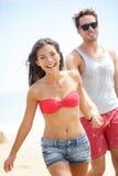 Lyckliga unga moderna kopplar ihop på strand Fotografering för Bildbyråer