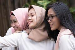Lyckliga unga muslim för grupp som tillsammans tar selfie royaltyfria bilder