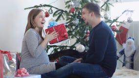 Lyckliga unga nätta par sitter nära den härliga dekorerade julgranen Maken ger en gåvaask till hans gravida fru arkivfoto