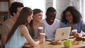Lyckliga unga olika vänner som har hållande ögonen på komedi för gyckel på bärbara datorn stock video