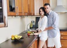 Lyckliga unga par har gyckel i modernt kök arkivfoto