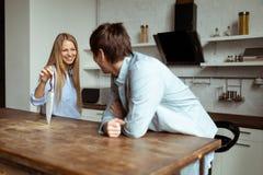 Lyckliga unga par har gyckel i modernt kök inomhus fotografering för bildbyråer