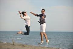 Lyckliga unga par har gyckel på strand Royaltyfria Bilder