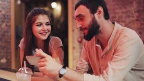 Lyckliga unga par med smartphonen som talar och dricker drycksammanträde på stången Vänner som använder mobiltelefonsmartphonen stock video