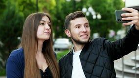 Lyckliga unga par på gatan som har video pratstund med vänner via mobiltelefonen arkivfilmer