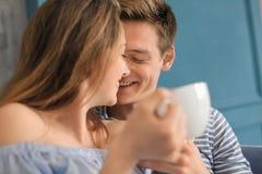 Lyckliga unga par som dricker varmt kaffe, medan vila hemma royaltyfria bilder