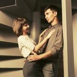 Lyckliga unga par som fl?rtar p? l?genheten arkivfoto