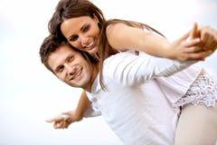 Lyckliga unga par som har gyckel Arkivfoton