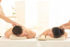 Lyckliga unga par som har massage i brunnsortsalong arkivbilder