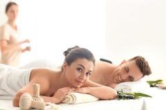 Lyckliga unga par som har massage i brunnsortsalong royaltyfri bild