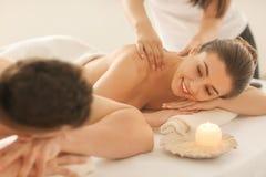 Lyckliga unga par som har massage i brunnsortsalong fotografering för bildbyråer