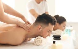 Lyckliga unga par som har massage i brunnsortsalong arkivfoto