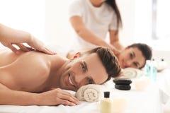 Lyckliga unga par som har massage i brunnsortsalong royaltyfria foton