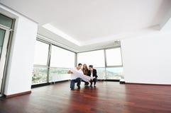 Lyckliga unga par som home köper Arkivbild