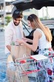 Lyckliga unga par som laddar livsmedelsbutikpåsar in i en bil royaltyfri bild