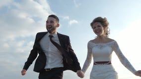 Lyckliga unga par som rymmer händer körda till och med ett brett fält och att ha rolig det fria bygd Man och kvinna som kör på lager videofilmer