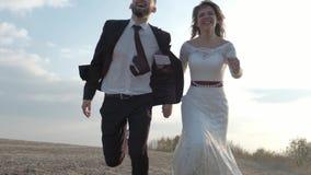 Lyckliga unga par som rymmer händer körda till och med ett brett fält och att ha rolig det fria bygd Man och kvinna som kör på stock video