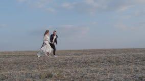 Lyckliga unga par som rymmer händer körda till och med ett brett fält och att ha rolig det fria bygd Man och kvinna som kör på arkivfilmer