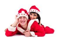 Lyckliga unga par som slitage Santa Claus kläder Arkivbild