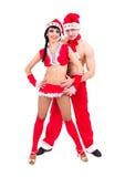 Lyckliga unga par som slitage Santa Claus kläder Fotografering för Bildbyråer