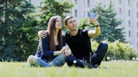 Lyckliga unga par som talar i video pratstund via mobiltelefonen som sitter på gräset parkerar och talar in, med vänner vid video arkivfilmer