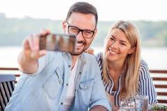 Lyckliga unga par som tar en selfie i ett kafé arkivbilder