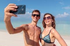 Lyckliga unga par som tar en selfie, klart bl?tt vatten som bakgrund kram arkivbilder